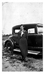 Anna Jakubcin Mikler stands beside a car on a farm in Slavia. 1930s, Black and White
