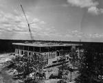Howard Phillips Hall under construction - workers on roof