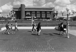 Library - students walk and bike in front of Reflecting Pond
